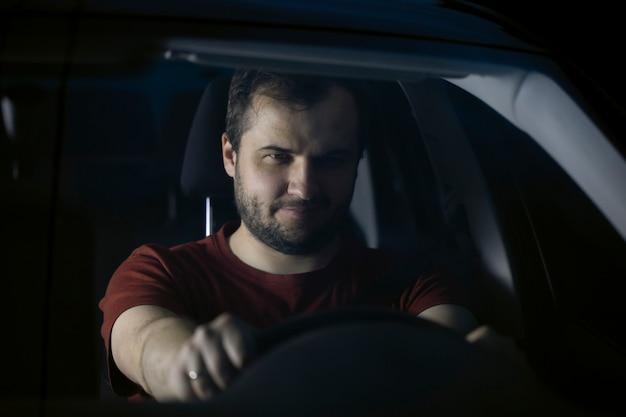 Com a barba por fazer, sério, jovem e sorridente motorista milenar sentado ao volante do carro à noite, olhando para o futuro, pensativo