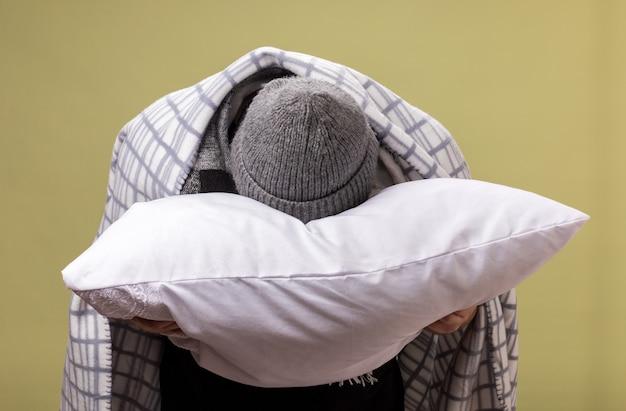 Com a cabeça baixa, um homem doente de meia-idade usando um chapéu de inverno e um lenço envolto em um travesseiro xadrez abraçado