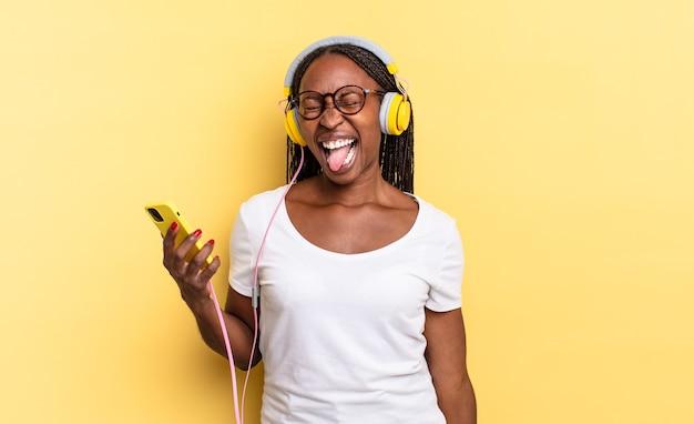 Com atitude alegre, despreocupada, rebelde, brincando e mostrando a língua, se divertindo e ouvindo música