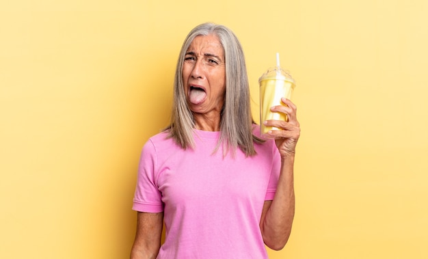Com atitude alegre, despreocupada, rebelde, brincando e mostrando a língua, se divertindo e segurando um milkshake