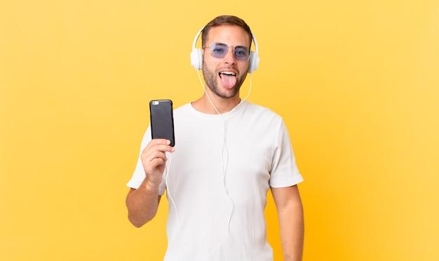 Com atitude alegre e rebelde, brincando e botando a língua para fora, ouvindo música com fones de ouvido e um smartphone