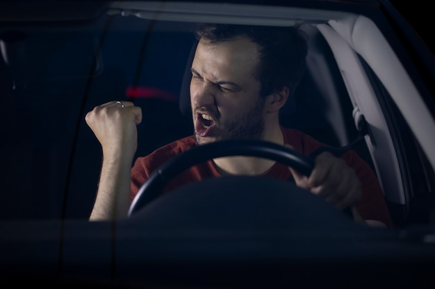 Com barba por fazer, jovem motorista milenar sério e confiante sentado ao volante do carro à noite gesticulando satisfatoriamente