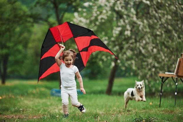 Com cachorro fofo. criança do sexo feminino positiva correndo com pipa de cor vermelha e preta nas mãos ao ar livre