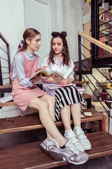 Com curiosidade. garotas elegantes e arrumadas usando tênis enquanto estão sentadas em escadas de madeira e discutindo informações no livro