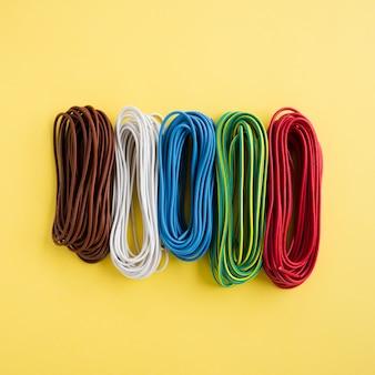 Com fios coloridos dispostos em uma fileira no pano de fundo amarelo