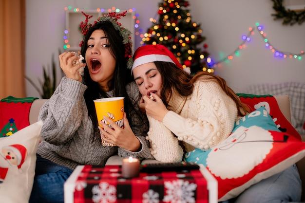 Com fome linda jovem com coroa de azevinho come pipoca e olha para a amiga sonolenta, sentada na poltrona, aproveitando o natal em casa