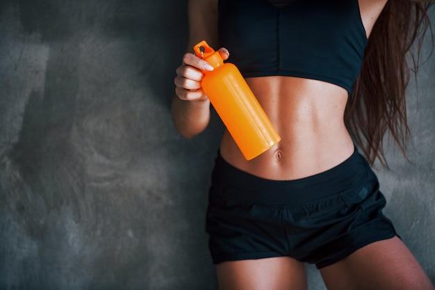 Com garrafa de água. mulher jovem fitness com tipo de corpo magro e com roupas esportivas pretas está no ginásio.