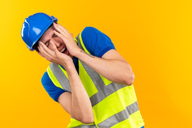 Com medo de fechar os olhos, o jovem construtor de uniforme cobriu o rosto com as mãos