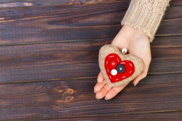Com o coração nas mãos em fundo de madeira. conceito dia dos namorados
