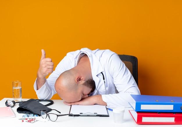 Com o jovem médico careca de cabeça baixa, vestindo túnica médica e estetoscópio sentado na mesa de trabalho com ferramentas médicas, o polegar levantado em laranja