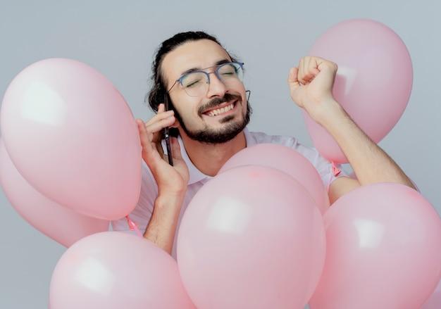 Com olhos fechados alegre homem bonito de óculos em pé entre balões e fala ao telefone isolado no branco