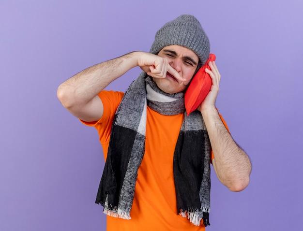 Com olhos fechados, jovem doente usando chapéu de inverno com lenço colocando uma bolsa de água quente na bochecha e limpando o nariz com a mão isolada no fundo roxo