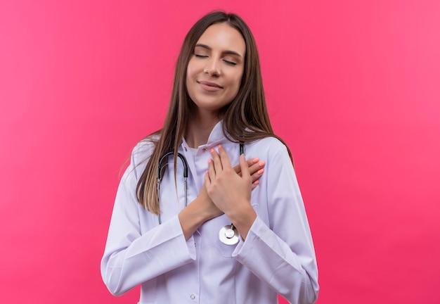 Com os olhos fechados, a jovem médica satisfeita usando um estetoscópio bata médica colocou as mãos no coração na parede rosa isolada