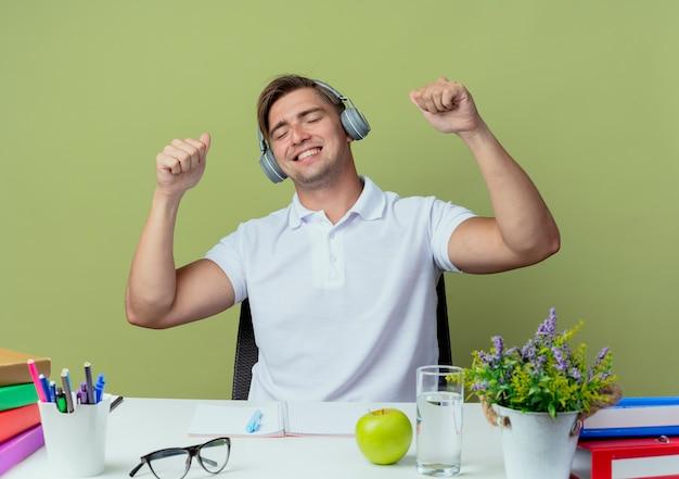 Com os olhos fechados, alegre jovem bonito estudante do sexo masculino sentado na mesa com as ferramentas da escola, usando fones de ouvido e ouvindo música isolada em verde oliva