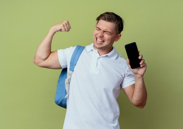 Com os olhos fechados, alegre, jovem bonito estudante do sexo masculino usando uma bolsa, segurando o telefone e mostrando um gesto de sim isolado em verde oliva