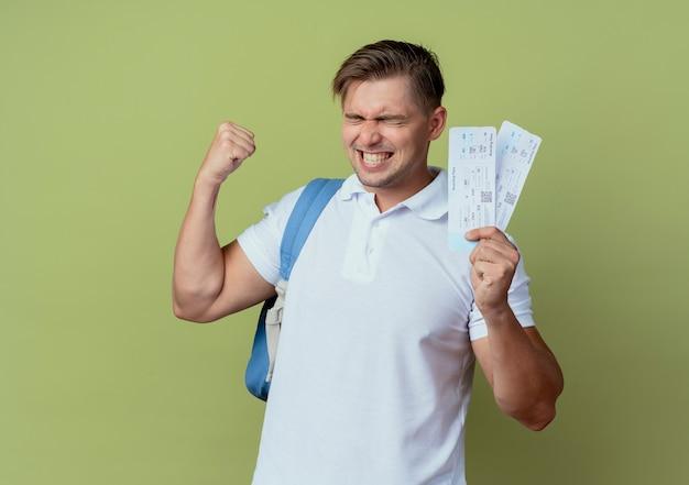 Com os olhos fechados, alegre jovem bonito estudante do sexo masculino vestindo uma bolsa com os ingressos e mostrando um gesto de sim isolado em verde oliva