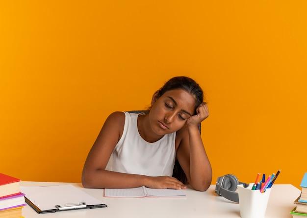 Com os olhos fechados, cansada jovem colegial sentada na mesa com as ferramentas da escola colocando a cabeça na mão em laranja