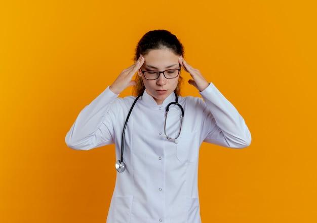 Com os olhos fechados, cansada jovem médica vestindo bata médica e estetoscópio com óculos colocando as mãos na têmpora isolada