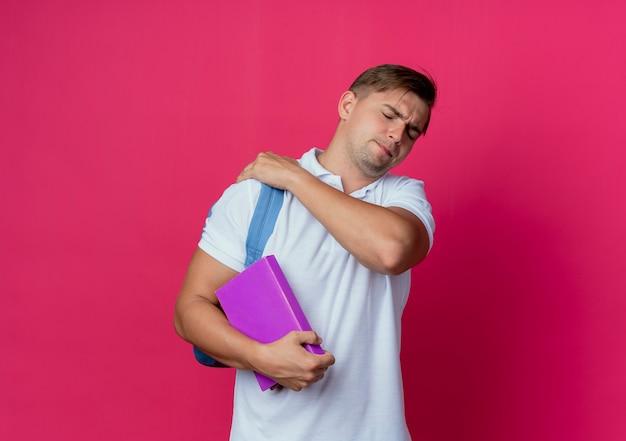 Com os olhos fechados cansado, jovem bonito estudante do sexo masculino usando uma mochila segurando livros