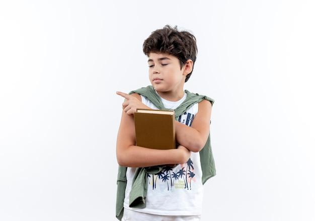 Com os olhos fechados, garotinho segurando um livro e apontando para o lado