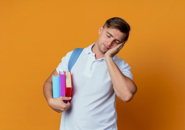 Com os olhos fechados, jovem bonito estudante do sexo masculino usando uma mochila segurando livros
