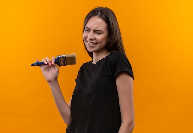 Com os olhos fechados, jovem caucasiana vestindo uma camiseta preta segurando um pincel e fingindo que canta na parede laranja isolada