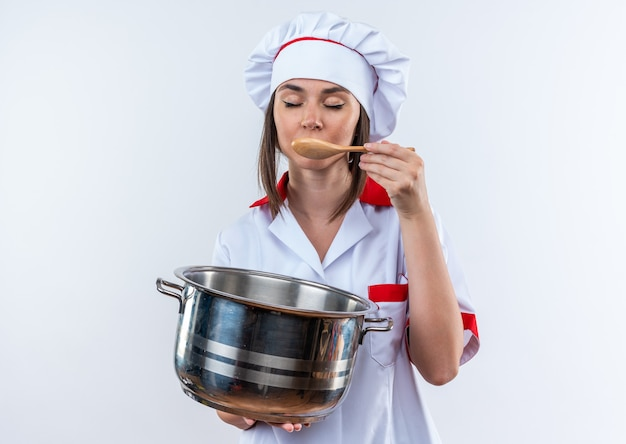 Com os olhos fechados, jovem cozinheira vestindo uniforme de chef segurando uma panela, tentando sopa com uma colher isolada no fundo branco