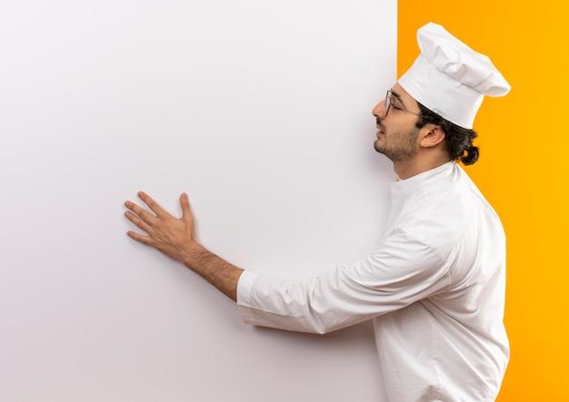 Com os olhos fechados, jovem cozinheiro usando uniforme de chef e óculos segurando uma parede branca isolada em uma parede amarela com espaço de cópia