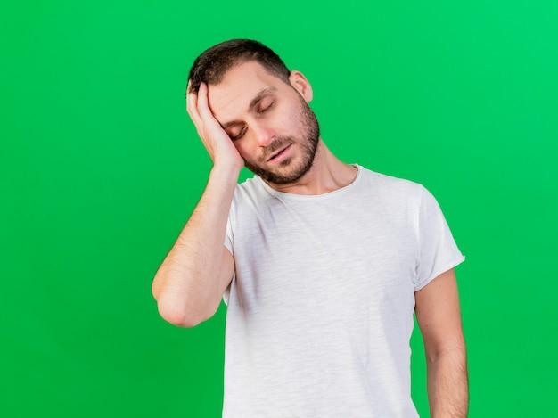 Com os olhos fechados, jovem doente colocando a mão no rosto isolado no fundo verde