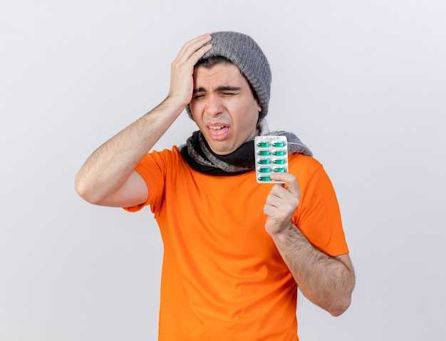 Com os olhos fechados, jovem doente com chapéu de inverno e lenço segurando comprimidos