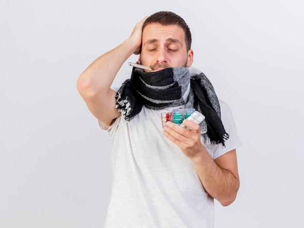 Com os olhos fechados, jovem doente com um lenço embrulhado em xadrez segurando comprimidos