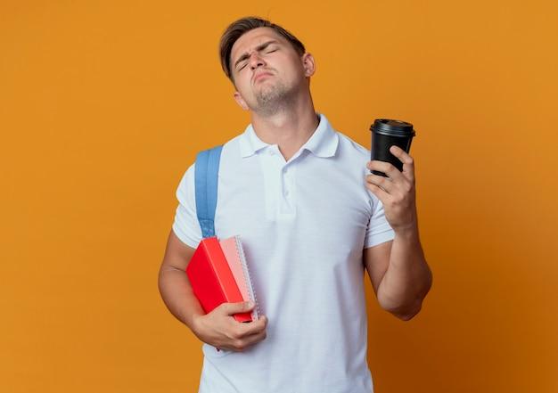 Com os olhos fechados, jovem e bonito estudante do sexo masculino vestindo uma mochila segurando um livro