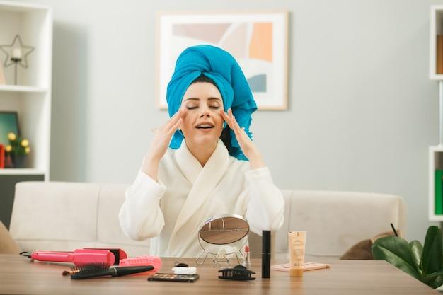 Com os olhos fechados, jovem enrolada no cabelo em uma toalha, aplicando creme de tonificação, sentada à mesa com ferramentas de maquiagem na sala de estar
