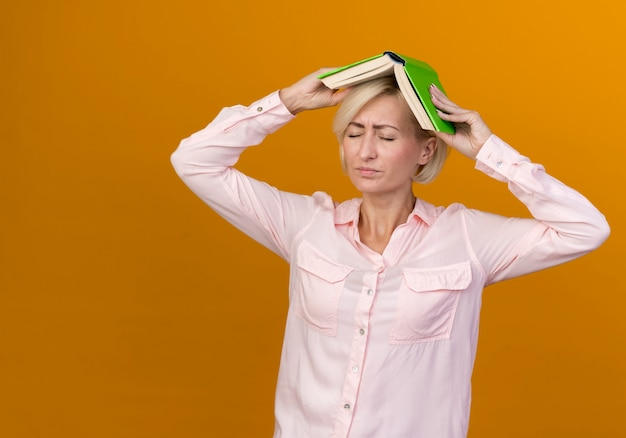 Com os olhos fechados, jovem eslava loira descontente cobriu a cabeça com um livro isolado na parede laranja