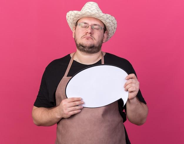Com os olhos fechados, jovem jardineiro usando um chapéu de jardinagem segurando um balão de fala isolado na parede rosa