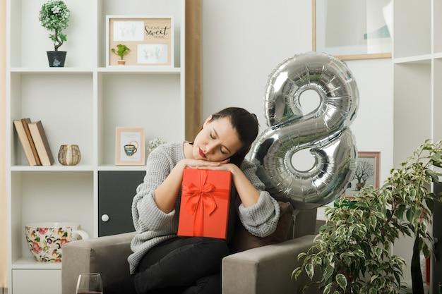 Com os olhos fechados, linda garota no dia da mulher feliz segurando um presente sentado na poltrona na sala de estar