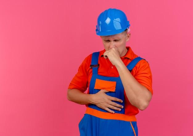 Com os olhos fechados, o jovem construtor masculino vestindo uniforme e capacete de segurança na cor rosa