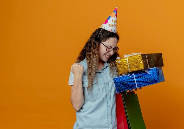 Com os olhos fechados, uma jovem alegre usando óculos e boné de aniversário segurando caixas de presente