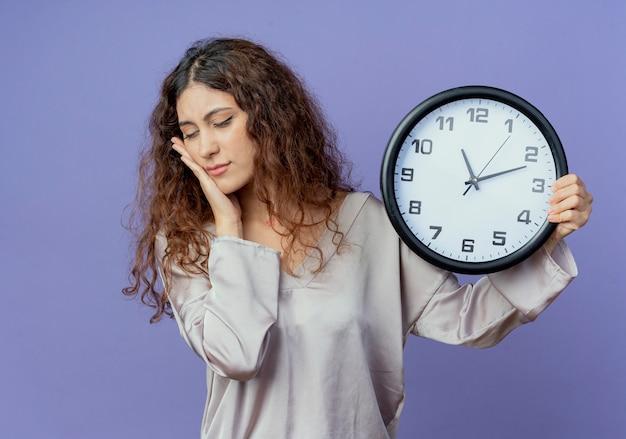 Com os olhos fechados, uma jovem bonita segurando um relógio de parede e colocando a mão na bochecha isolada na parede azul