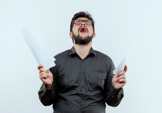 Com os olhos fechados, zangado, jovem empresário usando óculos e segurando papéis isolados no branco
