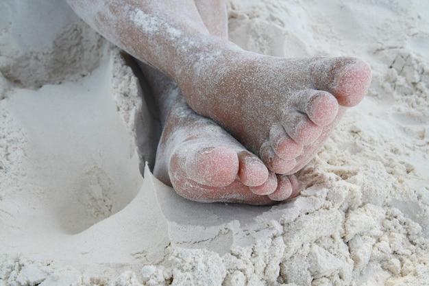 Com os pés descalços na praia de areia