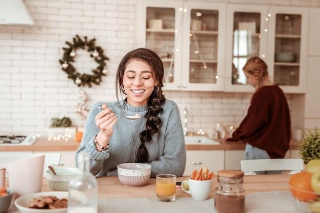 Com ótimo humor. uma garota afro-americana atraente de cabelos compridos tomando café da manhã enquanto sua amiga loira trabalhava atrás