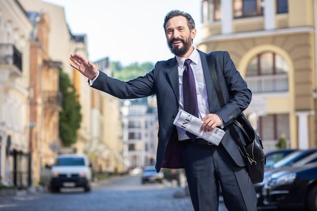 Com pressa. empresário profissional alegre parado na rua enquanto espera por uma carona