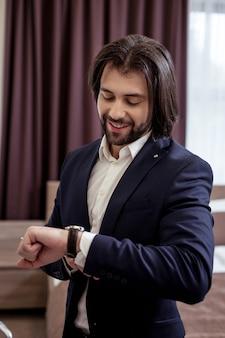 Com pressa. homem bonito alegre olhando as horas enquanto está com pressa