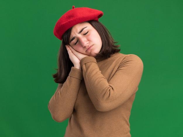 Com sono, jovem e bonita caucasiana com chapéu de boina coloca a cabeça nas mãos isoladas na parede verde com espaço de cópia