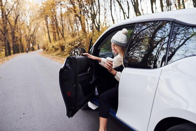 Com um copo de bebida nas mãos. menina tem viagem de outono de carro. automóvel novo moderno na floresta.