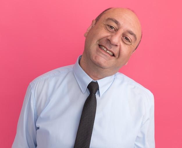 Com um homem de meia-idade inclinado vestindo uma camiseta branca com gravata isolada na parede rosa