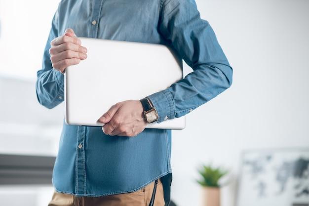 Com um laptop. feche a foto de um homem segurando um laptop