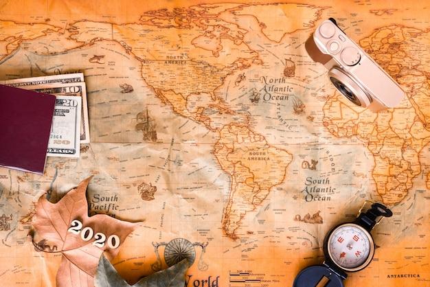 Com um mapa de fundo antigo e acessórios de viagem, viaje pelo mundo em 2020 na temporada de férias.