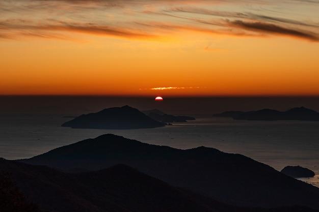 Com vista para uma silhueta de montanhas no mar durante o pôr do sol